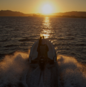 Amphibious vehicle navigating at sunset